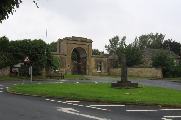 The Saxon Cross located on a green in the center of Follifoot on Main and Plompton streets, with the arched gateway of Rudding Gates behind it